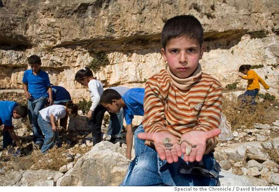 Judean Wilderness, South of Bethlehem: Muntasser, 7, a son of Bedouin, Mukhtar Abu Mussa, shows some of the ancient coins and artifacts he and his brothers and sisters found near their village as they search the area for antiquities.  David Blumenfeld/SPECIAL TO THE CHRONICLE Photo: David Blumenfeld