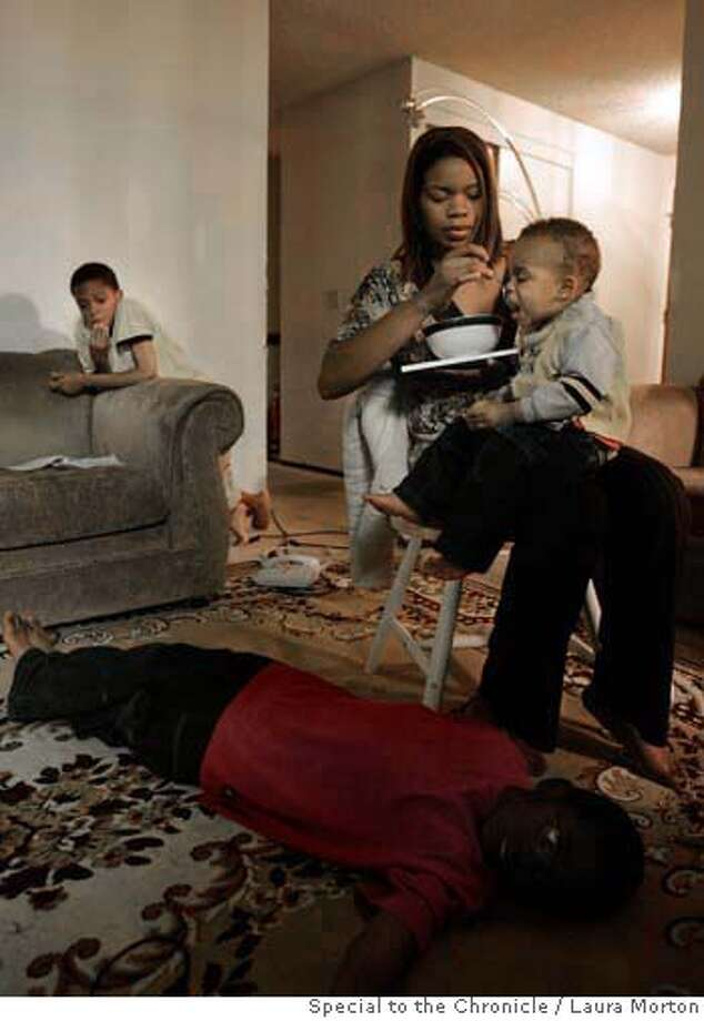 Fatemia Guice feeds her 16-month old son Amar� Guice as 11-year-old Aarol Guice (left) and 7-year-old Armon Lacy play in their Vallejo, CA home. Guice is a single mother of four sons, three of which have health problems. Her car recently broke down and she's worried about not being able to drive them to the hospital. Photo: Laura Morton