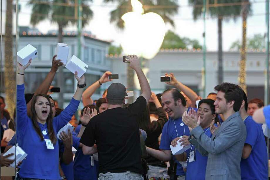 Apple Store employees cheer on customers Friday at the Highland Village location during its grand opening. Photo: Johnny Hanson / © 2012 Houston Chronicle