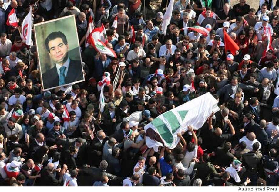 Lebanese mourners carry the coffin of Pierre Gemayel, wrapped in the flag of the Phalange Party and his picture during the funeral procession in Beirut, Lebanon, Thursday, Nov. 23, 2006. Tens of thousands of Lebanese gathered to bid farewell to an assassinated young Christian politician Thursday, and his anti-Syrian allies turned his funeral into a powerful show of force against opponents led by the militant Shiite Muslim Hezbollah and their Syrian backers. (AP Photo) Photo: STR