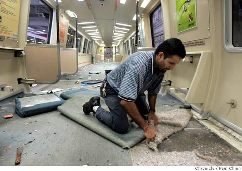 Lino Rodrigues removes carpeting from a BART car for retrofitting with composite flooring at the transit