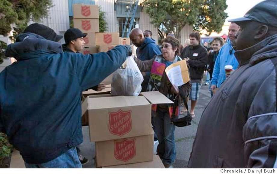 turkey_salvation_026_db.jpg  Salvation Army volunteer Billie Glendinning, 56, of San Francisco, receives packed Thanksgiving meals from Salvation Army workers, that she and volunteer Russell Gate, 40, of San Francisco, back right (partially hidden), will deliver early in the morning to residents in the Tenderloin district of San Francisco, CA, on Thursday, November, 23, 2006. 11/23/06  Darryl Bush / The Chronicle ** Billie Glendinning, Russell Gate (cq) Photo: Darryl Bush