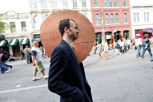 Chris Bucheit, 29, takes in the sights on 6th Street while wearing a cardboard penny on his head during South by Southwest on March 16, 2012, in Austin. Photo: EDWARD A. ORNELAS, Edward A. Ornelas/Express-News / © SAN ANTONIO EXPRESS-NEWS (NFS)