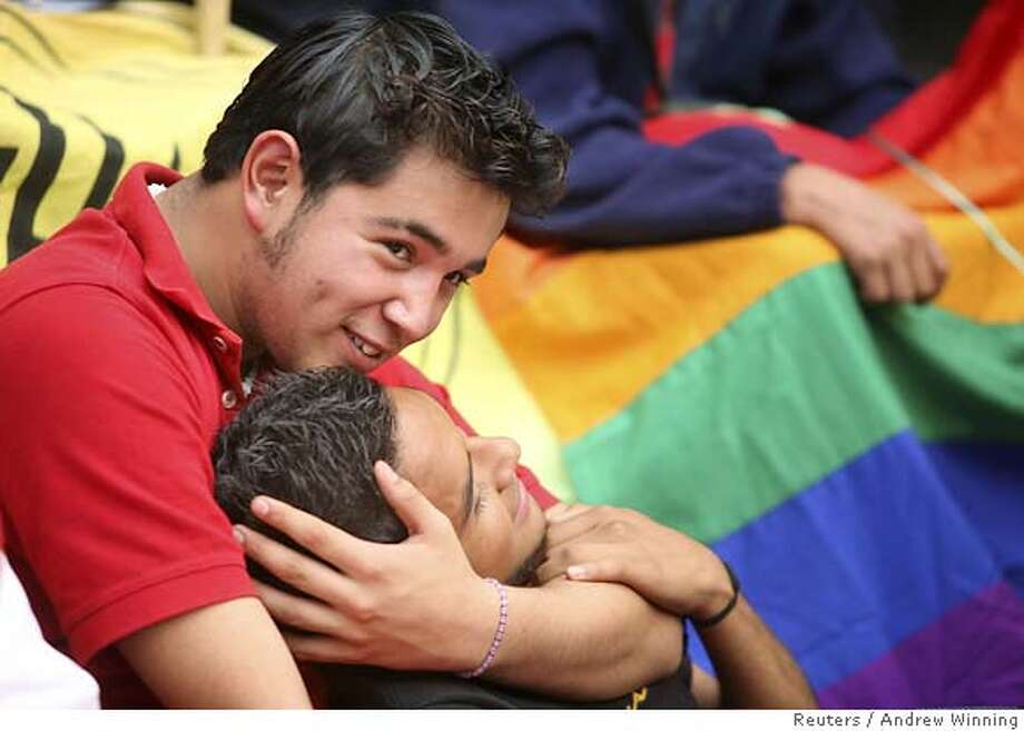 Ignacio and Carlos embrace as they sit on the steps of Mexico City's local legislature November 9, 2006 as law makers inside debate a bill which would approve same sex civil unions in the capital. REUTERS/Andrew Winning (MEXICO) 0 Photo: ANDREW WINNING