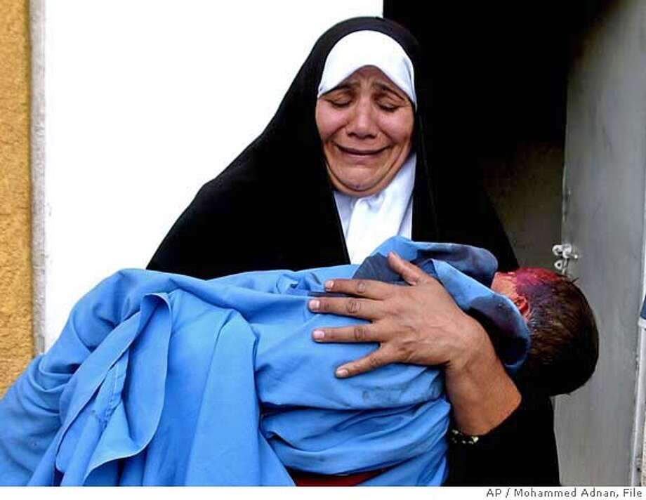 ** FILE ** A woman holds the lifeless body of her two-year-old grandson Jaafer Mohammed outside Baqouba's hospital, 60 kilometers (35 miles) northeast of Baghdad in this Oct. 31 2006 file photo. The United Nations said Wednesday Nov. 22, 2006 that 3,709 Iraqi civilians were killed in October, the highest monthly toll since the March 2003 U.S. invasion and another sign of the severity of Iraq's sectarian bloodbath. (AP Photo/Mohammed Adnan, File ) OCT. 31 2006 FILE PHOTO Photo: MOHAMMED ADNAN