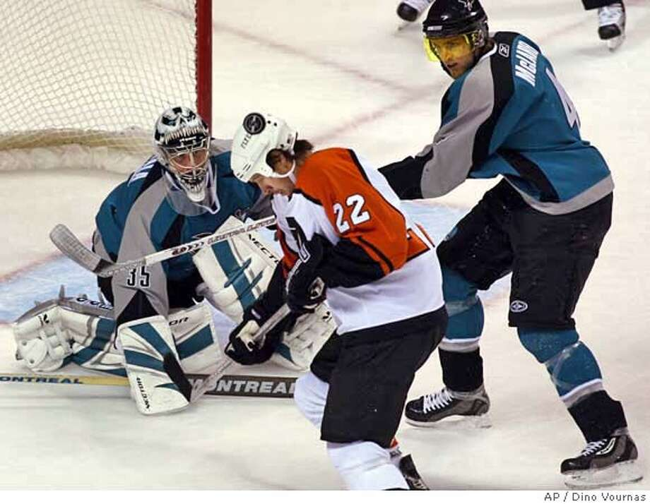 San Jose Sharks goalie Vesa Toskala, of Finland, watches the puck as teammate Kyle McLaren, right, works against Philadelphia Flyers' Mike Knuble (22) during the first period of an NHL hockey game Saturday, Nov. 18, 2006, in San Jose, Calif. (AP Photo/Dino Vournas) Photo: DINO VOURNAS
