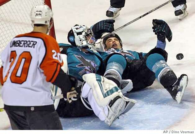 San Jose Sharks goalie Vesa Toskala, of Finland, blocks a shot by Philadelphia Flyers' Derian Hatcher, not seen, as San Jose's Rob Davison, right, tumbles over and Flyers' R.J. Umberger looks on in the first period of an NHL hockey game, Saturday, Nov. 18, 2006 in San Jose, Calif. (AP Photo/Dino Vournas) Photo: DINO VOURNAS
