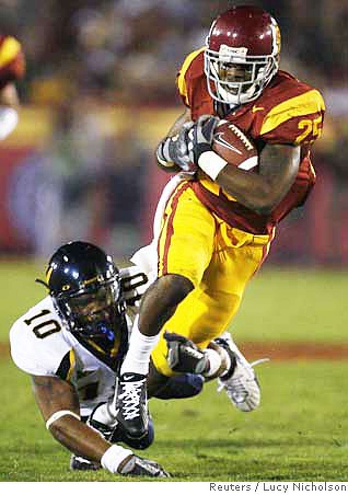 USC's C.J. Gable (R) is tackled by California's Desmond Bishop as he runs for a gain during the first quarter of their NCAA football game in Los Angeles November 18, 2006. REUTERS/Lucy Nicholson (UNITED STATES)