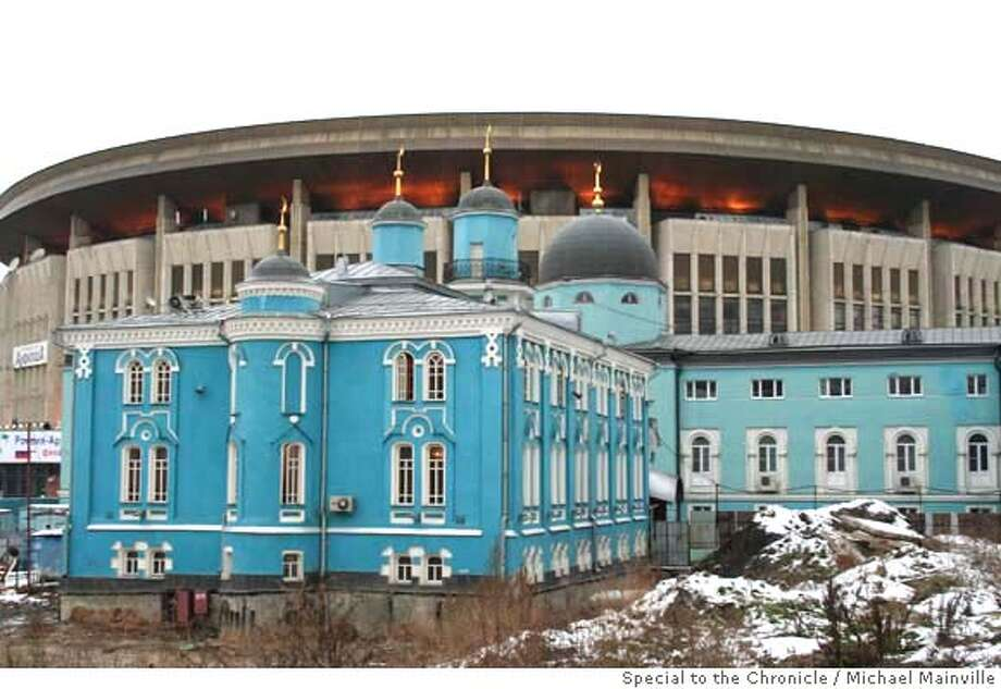 The Sobornaya Mosque sits in the shadow of the enormous grey complex built for Moscow's 1980 Olympics. Michael Mainville/Special to The Chronicle  Ran on: 11-19-2006  Sobornaya Mosque, overshadowed by Moscow's 1980 Olympics stadium, is one of four mosques for the capital's 2.5 million Muslims.  Ran on: 11-19-2006  Sobornaya Mosque, overshadowed by Moscow's 1980 Olympics stadium, is one of four mosques for the capital's 2.5 million Muslims. Photo: Michael Mainville