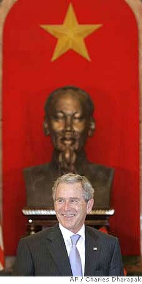A bust of revolutionary communist leader Ho Chi Minh is seen at rear as U.S. President George W. Bush smiles before the start of his meeting with Vietnamese President Nguyen Minh Triet, not pictured, at the presidential palace in Hanoi, Vietnam, Friday, Nov. 17, 2006. (AP Photo/Charles Dharapak) Photo: CHARLES DHARAPAK