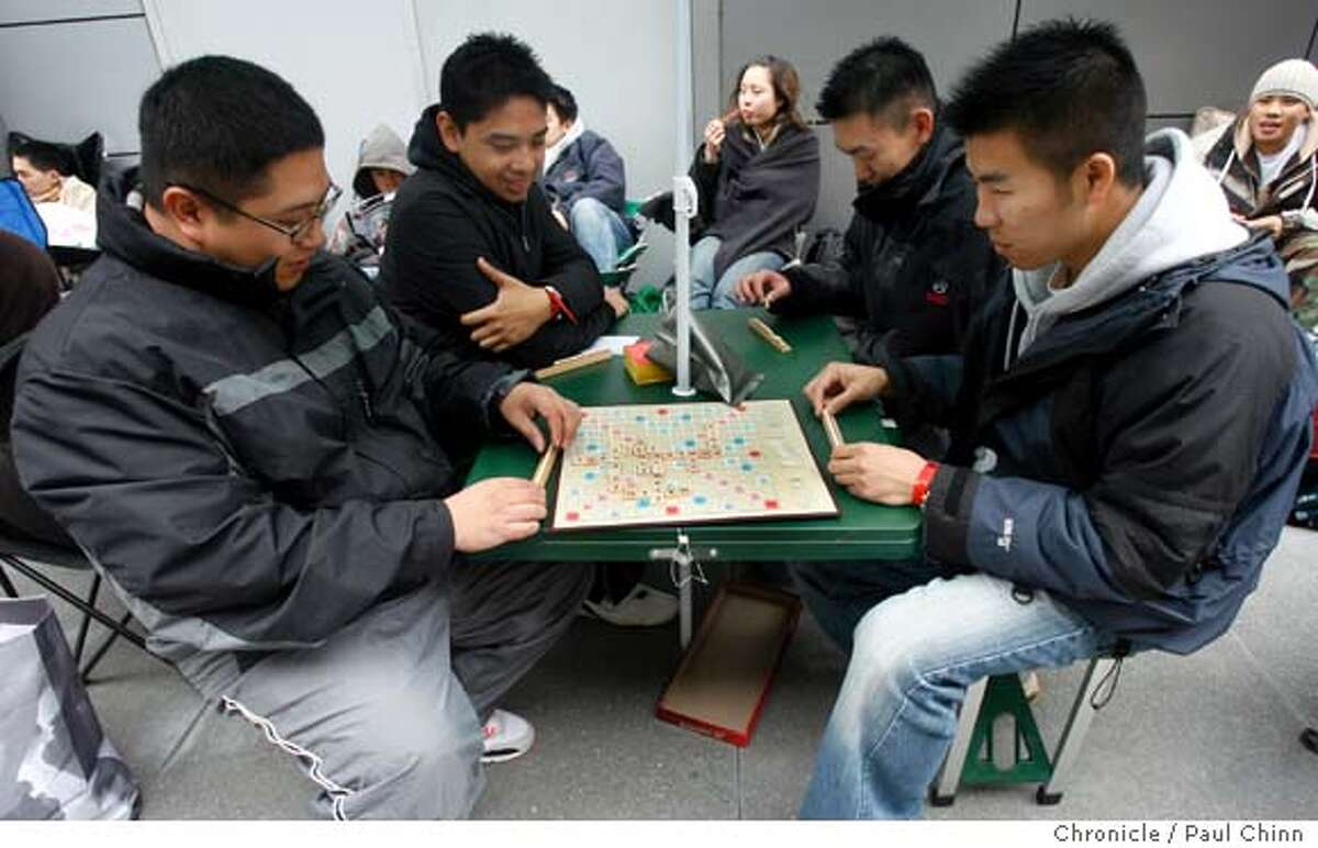 From left, David Giang, Chris Valiao, Vincent Chan and Eric Tong play an old-fashioned game of Scrabble while waiting in line to buy the next generation video game as enthusiasts wait in long lines to be the first to buy a Sony Playstation 3 video game console at Metreon in San Francisco, Calif. on Thursday, Nov. 16, 2006. About 500 units were to be made available for the diehards - some who arrived at 8 a.m. Wednesday. PAUL CHINN/The Chronicle **David Giang, Chris Valiao, Vincent Chan, Eric Tong