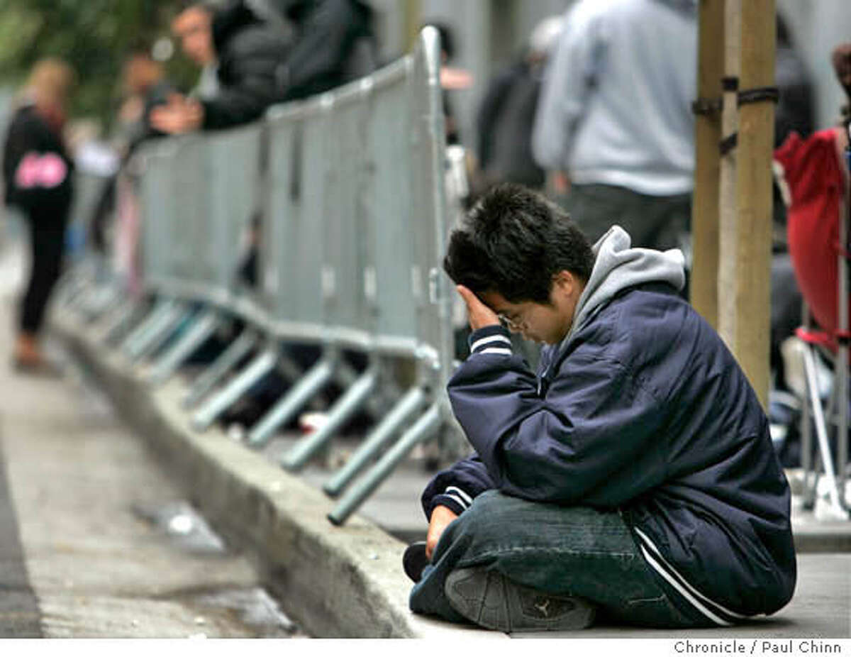Jacob Chen, who arrived at 6 a.m. Thursday, rests on the sidewalk while waiting in line to buy a Sony Playstation 3 video game console at Metreon in San Francisco, Calif. on Thursday, Nov. 16, 2006. About 500 units were to be made available for the diehards - some who arrived at 8 a.m. Wednesday. PAUL CHINN/The Chronicle **Jacob Chen