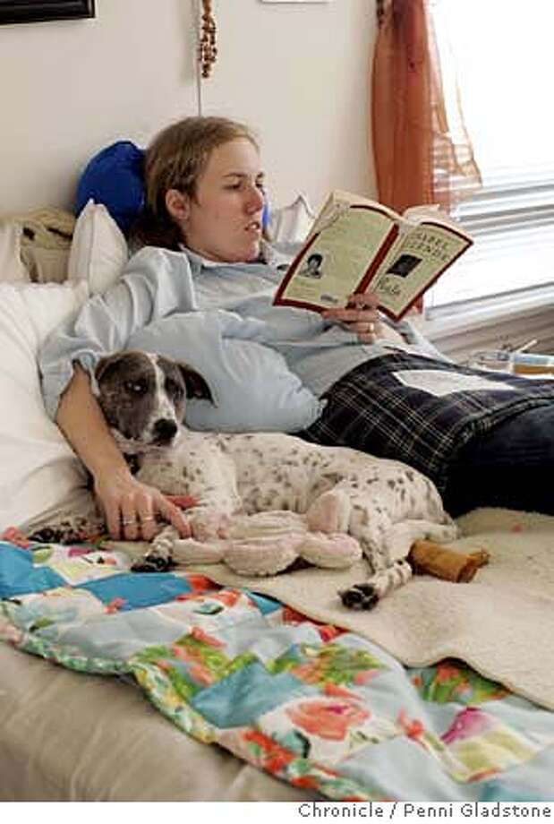 Alicia Parlette is tucked away in bed one afternoon at home during a period of withdrawls from one of her drugs. On her bed is her dog Clarabell. She is reading with a heat pad at her side where her tumor is. Event on 10/17/06 in San Francisco.  Penni Gladstone / The Chronicle MANDATORY CREDIT FOR PHOTOG AND SF CHRONICLE/ -MAGS OUT Photo: Penni Gladstone