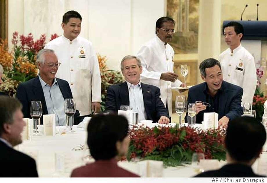 U.S. President George W. Bush, center, is seated between Singaporean Prime Minister Lee Hsien Loong, right, and Senior Minister Goh Chok Tong, left, during a dinner at the Istana in Singapore Thursday, Nov. 16, 2006. Bush is in Singapore for a two-day visit before traveling to Vietnam and Indonesia. (AP Photo/Charles Dharapak) Photo: CHARLES DHARAPAK