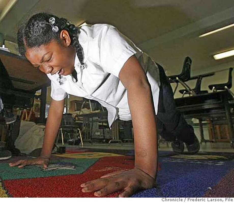 Kyeara Renee Rowel (10) gets down and does her push-ups as part of her physical fitness test at MalcolmX. The 5th graders at Malcolm X Elementary are gearing up for the STAR testing which is the yard stick of weather the school will last another year in the Hunter Point district of San Francisco. 4/4/06  Frederic Larson Photo: Frederic Larson