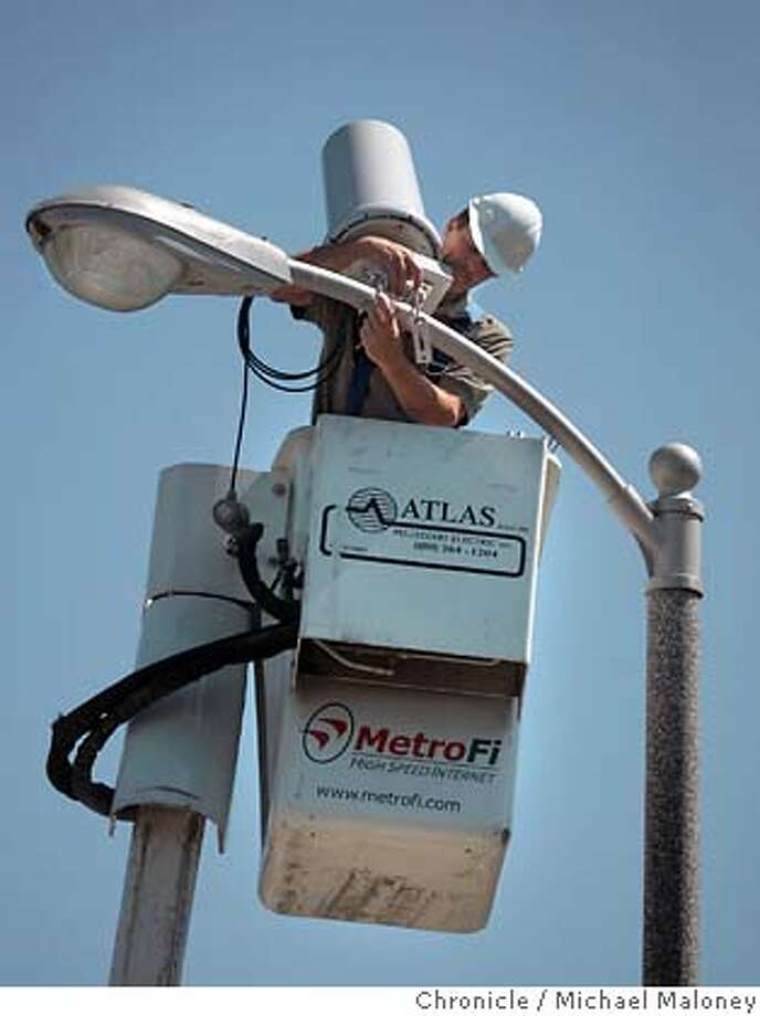 Glenn Arvin of Atlas/Pellizzari Electric Inc. installs a MetroFi antenna on a light pole near the Sunnyvale Library.  MetroFi has built and operates Wi-Fi wireless broadband networks in Cupertino, Santa Clara, and Sunnyvale California. Residents and businesses in these cities enjoy high-speed access to the Internet from anywhere in the community - without the use of wires or cables. The service is free, supported by local advertisers and delivers DSL-like speeds (about one megabit per second).  Photo by Michael Maloney / San Francisco Chronicle on 8/16/06 in Sunnyvale,CA  Ran on: 08-21-2006  Technology co-workers Dennis Ortman (left) and Bill Shafer use free MetroFi to access the Internet at a Starbucks in Cupertino. MANDATORY CREDIT FOR PHOTOG AND SF CHRONICLE/ -MAGS OUT Photo: Michael Maloney