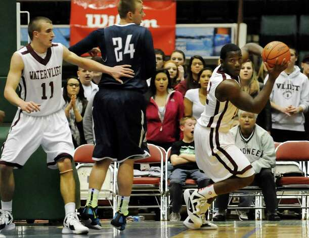 Watervliet's Antoine Johnson (12), right, controls the rebound against Burke Catholic's Stan Buczek (24) during their Class B state semifinal basketball game on Friday, March 16, 2012, at Glens Falls Civic Center in Glens Falls, N.Y. At left is Watervliet's Griffin Kelly. (Cindy Schultz / Times Union) Photo: Cindy Schultz / 00016822A