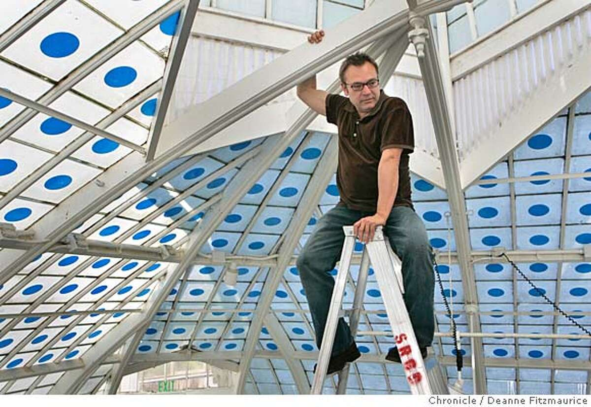 """visualart16_0084_df.jpg Stanlee is photographed high on a ladder with the blue dots which create the impression that the sky is penetrating through the glass roof of the Conservatory. Stanlee Gatti (cq) works on the installation of his new show, """"One: An Earth Installation by Stanlee Gatti"""" that reflects on the interconnectedness of all living things at the Conservatory of Flowers in Golden Gate Park. Photographed in San Francisco on 11/14/06. (Deanne Fitzmaurice/ The Chronicle) Mandatory credit for photographer and San Francisco Chronicle. /Magazines out."""