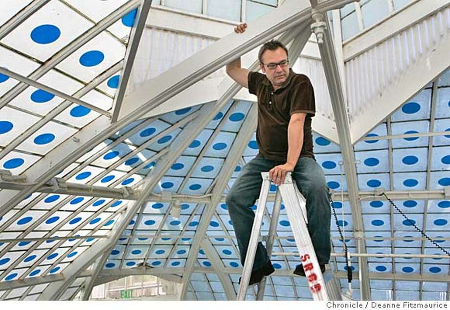 "visualart16_0084_df.jpg  Stanlee is photographed high on a ladder with the blue dots which create the impression that the sky is penetrating through the glass roof of the Conservatory. Stanlee Gatti (cq) works on the installation of his new show, ""One: An Earth Installation by Stanlee Gatti"" that reflects on the interconnectedness of all living things at the Conservatory of Flowers in Golden Gate Park. Photographed in San Francisco on 11/14/06. (Deanne Fitzmaurice/ The Chronicle) Mandatory credit for photographer and San Francisco Chronicle. /Magazines out. Photo: Deanne Fitzmaurice"