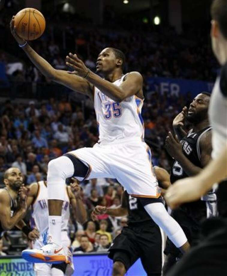Oklahoma City Thunder forward Kevin Durant (35) shoots in front of San Antonio Spurs center DeJuan Blair, right, in the third quarter of an NBA basketball game in Oklahoma City, Friday, March 16, 2012. (AP Photo/Sue Ogrocki) (AP)