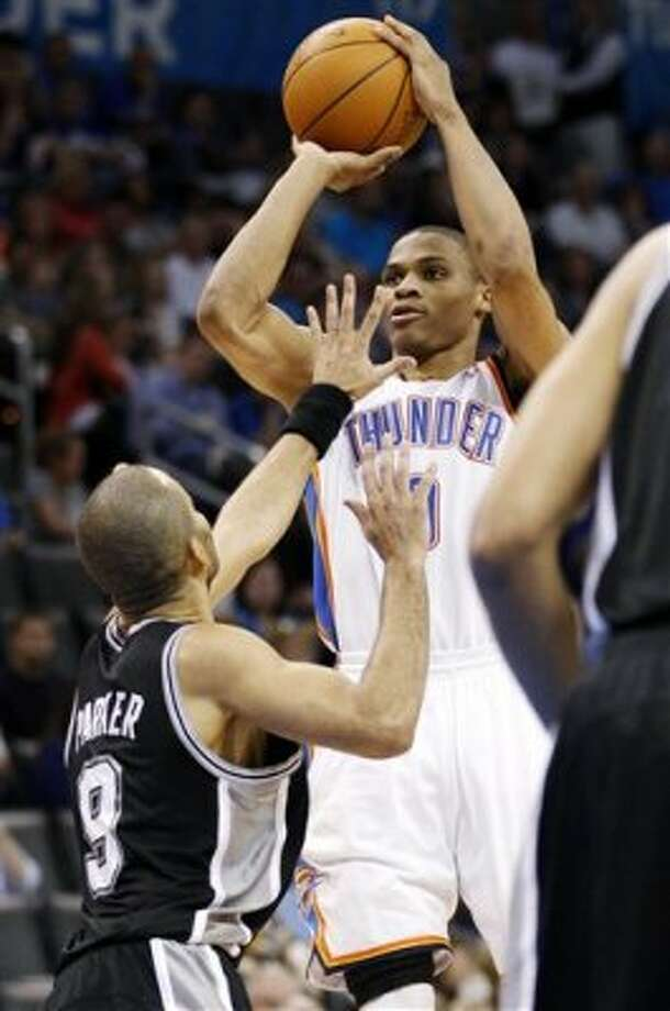 Oklahoma City Thunder guard Russell Westbrook, right, shoots over San Antonio Spurs guard Tony Parker (9), of France, in the third quarter of an NBA basketball game in Oklahoma City, Friday, March 16, 2012. (AP Photo/Sue Ogrocki) (AP)