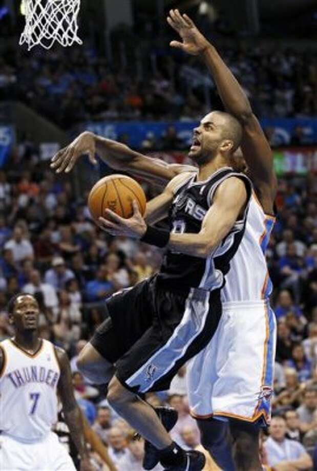 San Antonio Spurs guard Tony Parker, center, of France, is fouled by Oklahoma City Thunder forward Serge Ibaka, right, of Republic of Congo, as he shoots in the second quarter of an NBA basketball game in Oklahoma City, Friday, March 16, 2012. Thunder guard Royal Ivey is at left. (AP Photo/Sue Ogrocki) (AP)