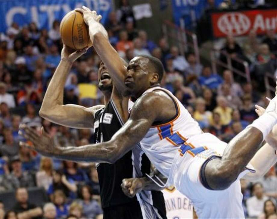 Oklahoma City Thunder center Kendrick Perkins, right, fouls San Antonio Spurs forward Tim Duncan, left, as he shoots in the first quarter of an NBA basketball game in Oklahoma City, Friday, March 16, 2012. (AP Photo/Sue Ogrocki) (AP)