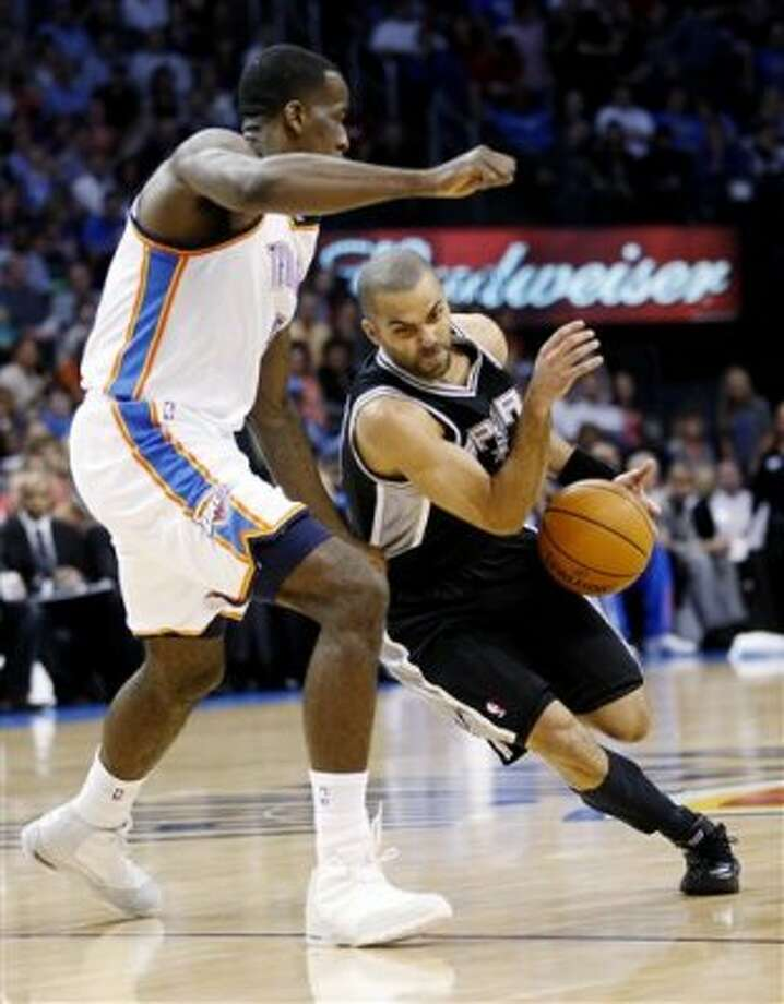 San Antonio Spurs guard Tony Parker, right, of France, drives around Oklahoma City Thunder center Kendrick Perkins, left, in the first quarter of an NBA basketball game in Oklahoma City, Friday, March 16, 2012. (AP Photo/Sue Ogrocki) (AP)