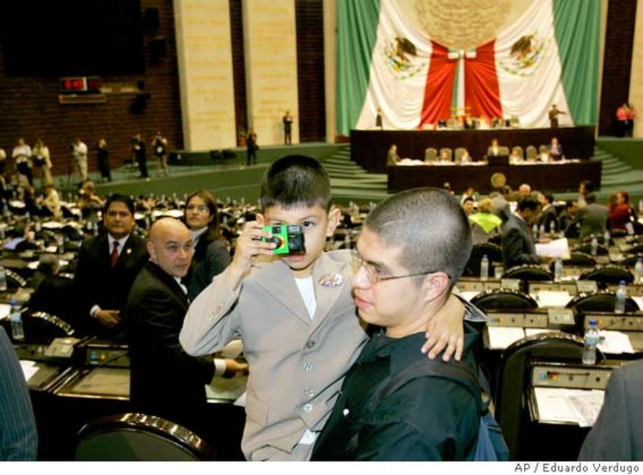 Saul Arellano, 7, of Chicago takes a picture while being held by an unidentified man at the Mexican Congress in Mexico City, Mexico, Tuesday, Nov. 14, 2006. Four-foot-tall (1.2-meter-tall) second-grader Saul Arellano, a U.S. citizen, appeared in the 500-member lower house of the Mexican Congress on Tuesday to plead for lawmakers' help in lobbying Washington to stop the deportation of his migrant mother, who has taken refuge in a Chicago church. (AP Photo/Eduardo Verdugo) **EFE OUT** RETRANSMITTING TO ADD THAT MAN CARRYING BOY IS UNIDENTIFIED ** Photo: EDUARDO VERDUGO