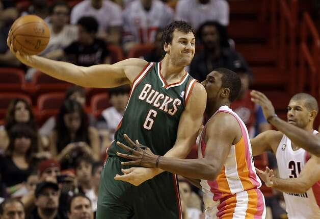 Milwaukee Bucks' Andrew Bogut (6) looks to pass as Miami Heat's Mario Chalmers, center, defends during the first half of an NBA basketball game, Sunday, Jan. 22, 2012, in Miami. The Bucks defeated the Heat 91-82. At right is Miami Heat's Shane Battier (31).(AP Photo/Lynne Sladky) Photo: Lynne Sladky, ASSOCIATED PRESS