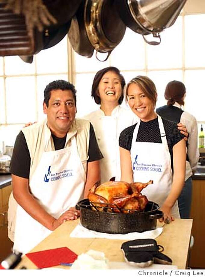 TURKEYCAMP15_385_cl.JPG  Turkey training camp at the San Francisco Chronicle Food kitchen. Olivia Wu and Tara Duggan teach five people how to make a Thanksgiving dinner. Photo left-right: Art Gutierrez, Olivia Wu, and Tara Monar with their freshly roasted turkey from the oven.  photo by Craig Lee / The Chronicle  Ran on: 11-12-2006 Ran on: 11-15-2006  Art Gutierrez (left) and Tara Molnar show off their freshly roasted turkey that Olivia Wu (center) taught them how to prepare at The Chronicle's Turkey Training Camp. Photo: Photo By Craig Lee