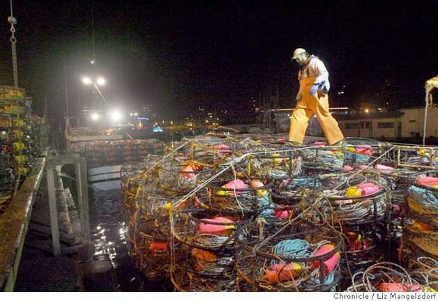 Fisherman Ken Strombeck works tying down the crab pots before dawn on the Phantom, a boat out of Moss Landing, on the morning of Nov. 14, 2006. The fishermen by the piers were waiting to see if the crab boats would go out. The boat is docked by Pier 45.  Liz Mangelsdorf / The Chronicle Photo: Liz Mangelsdorf