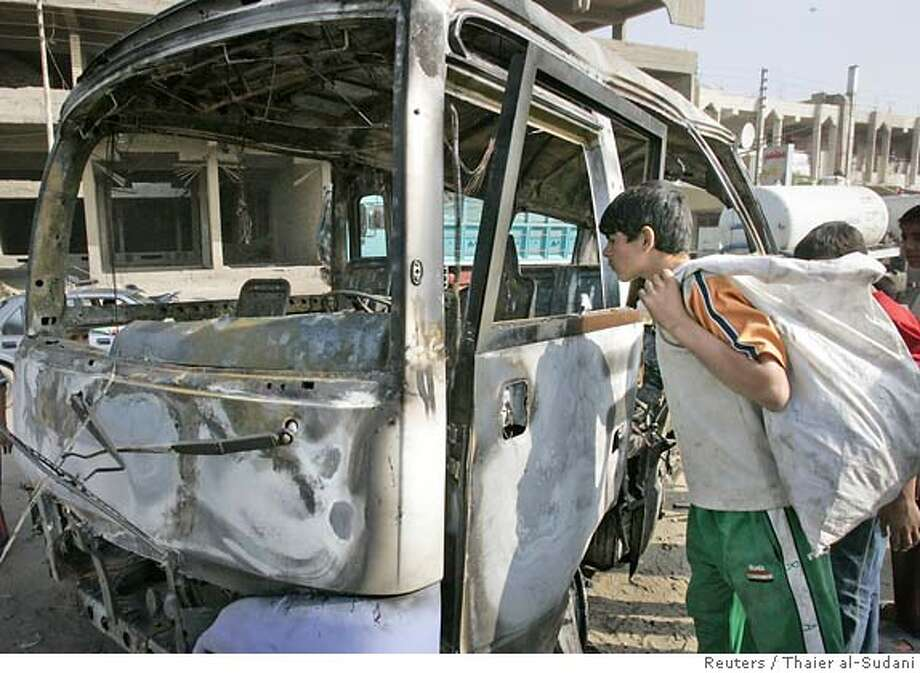 Residents look at a burnt mini-bus after a suicide bomb attack in Baghdad, November 13, 2006. A blast in a mini-bus caused by a suicide bomber killed 11 people and wounded 18 more in the northern district of Shaab in Baghdad, police said. REUTERS/Thaier al-Sudani (IRAQ) 0 Photo: THAIER AL-SUDANI