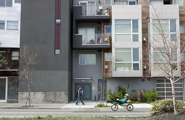 People tread past the new housing buildings on San Pablo Street in Oakland on Saturday. New buildings on the west side of San Pablo Street in Oakland indicate regional growth. Photo: Kevin Johnson, The Chronicle