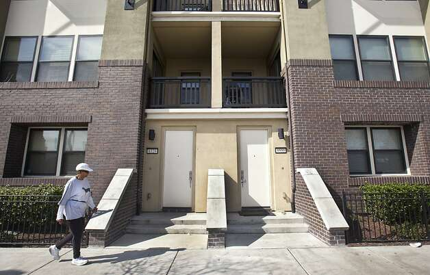 A woman walks past one of the new housing buildings on San Pablo Street in Oakland on Saturday. New buildings on the west side of San Pablo Street in Oakland indicate regional growth. Photo: Kevin Johnson, The Chronicle