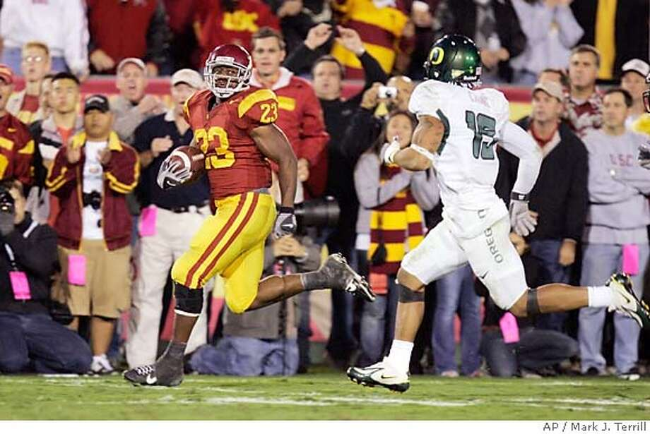 Southern California running back Chauncey Washington rushes for a 43-yard touchdown as Oregon cornerback Patrick Chung gives chase during the second half of a football game Saturday night, Nov. 11, 2006, in Los Angeles. (AP Photo/Mark J. Terrill) EFE OUT Photo: MARK J. TERRILL