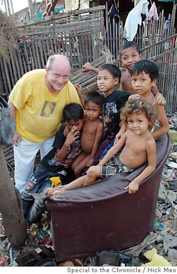 Marc Gold, left, with slum dwellers in Cambodia. Marc Gold, philanthropist from San Francisco who raises money in California from friends and colleagues, then roams Asia in search of needy causes to give it away to.  Nick Meo/Special to The Chronicle Photo: Nick Meo