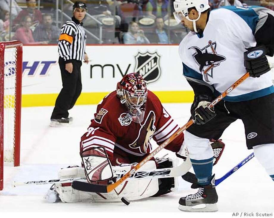Phoenix Coyotes goalie Curtis Joseph, left, makes the save on San Jose Sharks right winger Jonathan Cheechoo, right, during the first period of an NHL hockey game Saturday, Nov. 11, 2006, in Glendale, Ariz. (AP Photo/Rick Scuteri) Photo: RICK SCUTERI