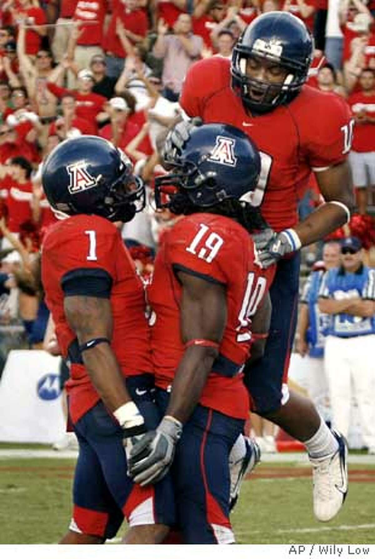 Arizona's Chris Henry (19) is congratulated by teammates Syndric Steptoe (1) and Michael Thomas, behind, after scoring a touchdown in the third quarter against California in a college football game on Saturday, Nov. 11, 2006, in Tucson, Ariz. Arizona won, 24-20. (AP Photo/ Wily Low)
