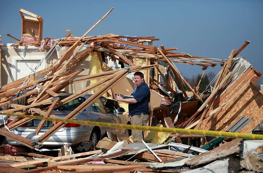 Insurance agents assess the damage to the home of 87-year-old William Harvey Dusbiber in Dexter, Michigan, Friday, March 16, 2012. A tornado roared through the neighborhood of Huron Farms a day earlier. (Regina H. Boone/Detroit Free Press/MCT)