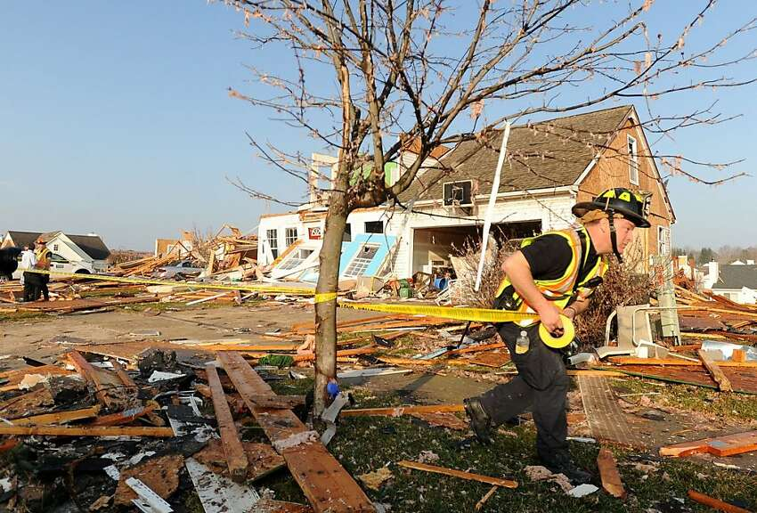 A Dexter firefighter tapes off the most damaged houses in Huron Farms neighborhood after a tornado hit Dexter, Mich. on March 16, 2012. The twister that took aim at this Michigan village unleashed winds of 135 mph and lingered on the ground for a full half-hour, plowing a path of destruction that stretched for 10 miles. ( AP Photo/AnnAbor.Com, Angela J. Cesere)