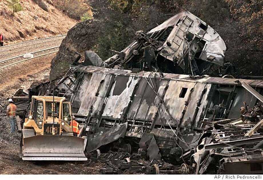 Two of six derailed train cars are seen near Baxter, Calif., Friday, Nov. 10, 2006. Authorities on Friday found the body of a missing railway worker buried in the smoldering wreckage of a Union Pacific train that derailed in the Sierra Nevada a day earlier. The discovery brings the death toll from Thursday's crash to two, ranking it among the deadliest Union Pacific accidents in California in recent years. (AP Photo/Rich Pedroncelli) Photo: RICH PEDRONCELLI