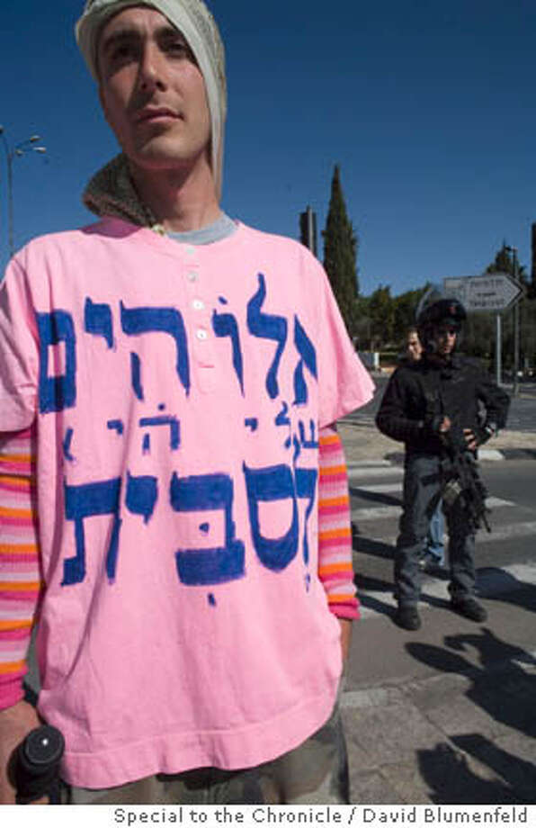 "Jerusalem, Israel: David Sheen, an Israeli gay activist from Oakland, California (interviewed) along with a group of gay activists, gathered in an attempt to march in an illegal gay pride parade in Jerusalem. Sheen's t-shirt reads ""My god is a lesbian."" The march was cancelled by Police after Ultra Orthodox Jews rioted all week in protest of the parade, and a rally was held instead at the Givat Ram stadium. Sheen posed in front of riot police and was later arrested at the illegal march.  David Blumenfeld/Special to The Chronicle  Ran on: 11-11-2006  David Sheen, an activist from Oakland whose shirt reads, &quo;My God is a lesbian,&quo; was arrested in Jerusalem before a gay pride rally. Photo: David Blumenfeld"