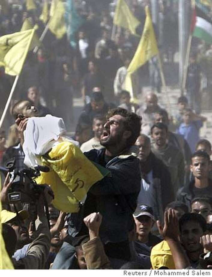 "A Palestinian man cries as he carries the body of one-and-a-half-year-old Maram Al-Athamna, who was killed together with her family by Israeli artillery shell, during her funeral at Beit Hanoun town in the northern Gaza Strip November 9, 2006. Tens of thousands of Palestinians marched through Gaza on Thursday in funeral processions for 18 people killed by Israeli shelling on what one militant faction called ""a day of tragedy beyond imagination"". REUTERS/Mohammed Salem (GAZA) 0 Photo: MOHAMMED SALEM"
