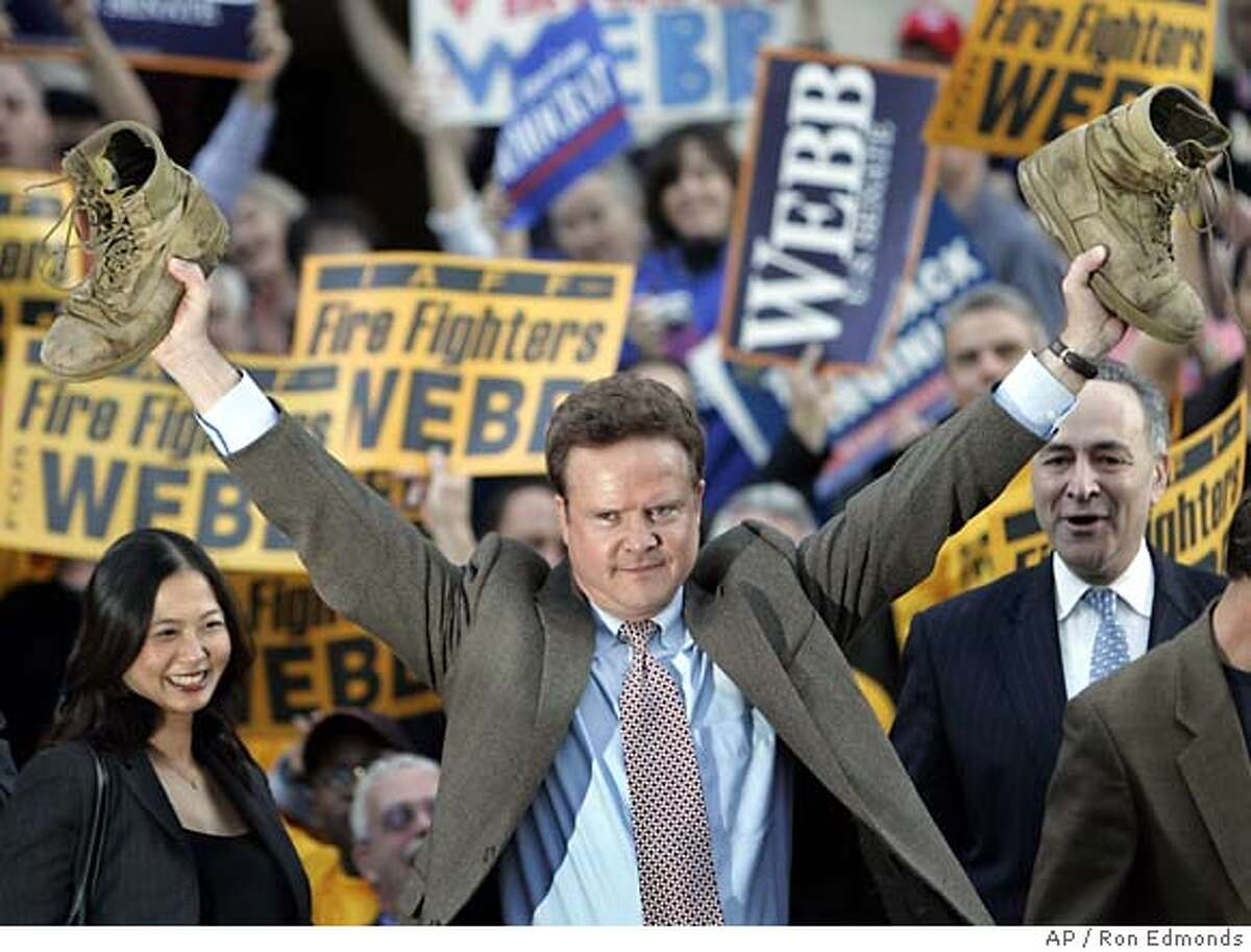 Holding up combat boots worn by his son, a Marine serving in Iraq, Democrat Jim Webb announces his victory in Virginia's pivotal Senate race, giving the Democrats total control of both the House and Senate for the first time in 12 years, at Courthouse Plaza in Arlington, Va., Thursday, Nov. 9, 2006. A 60-year-old Naval Academy graduate, novelist and decorated Vietnam veteran who served as Navy secretary under former President Reagan, Webb bitterly opposed the war in Iraq and switched to the Democratic Party. He is joined at left by his wife Hong Le Webb and at right by Sen. Charles Schumer, D-NY. (AP Photo/Ron Edmonds)