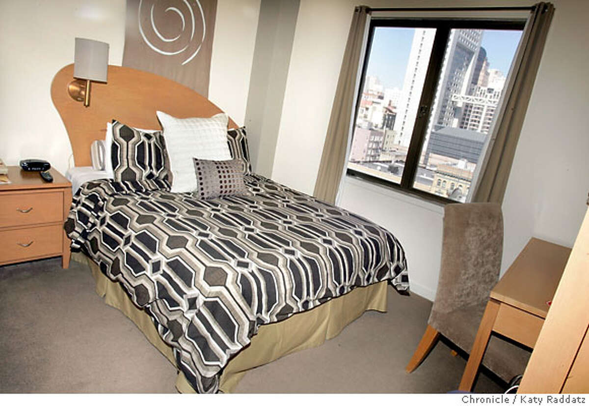 HOTELS_METROPOLIS_012_RAD.jpg SHOWN: A cute room with a view of the city and a double bed--this room is up high, on the tenth floor. Each floor has a theme--this floor is the wind floor. The Metropolis Hotel, 25 Mason St. and 16 Turk St. in San Francisco. These photos were made on Wednesday, Oct. 18 2006, in San Francisco, CA. (Katy Raddatz/San Francisco Chronicle) **Metropolis Hotel Ran on: 11-09-2006 The side of Hotel Metropolis from Mason Street, above left. Each floor of the hotel has a different theme, such as this 10th-floor wind room, right. Below, the bathrooms are basic: large, white with accent tiles. But you do get a welcome kit that includes toiletries. Ran on: 11-09-2006