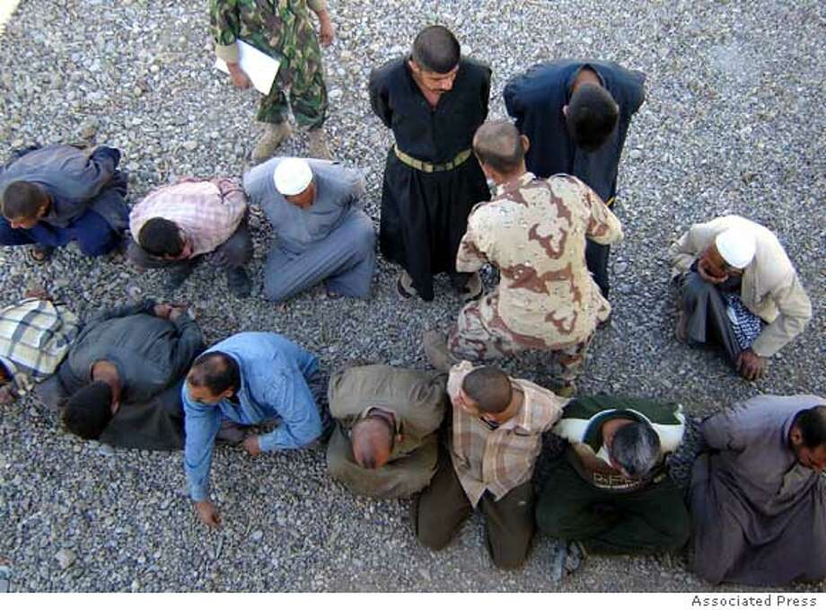 Iraqi soldiers guards detainees in Baqouba, 60 kilometers (35 miles) northeast of Baghdad, Iraq, Wednesday, Nov. 8, 2006. Iraqi military killed three suspected militants and detained 13 others in a raid. (AP Photo)