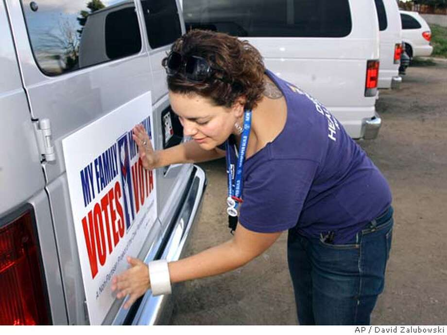 Leah Bry hangs a sign promoting the amendment to increase the minimum wage in Colorado on the back of a van used by Mi Familia Vota in southwest Denver on Friday, Nov. 3, 2006. (AP Photo/David Zalubowski) NOV. 3, 2006 PHOTO Photo: DAVID ZALUBOWSKI