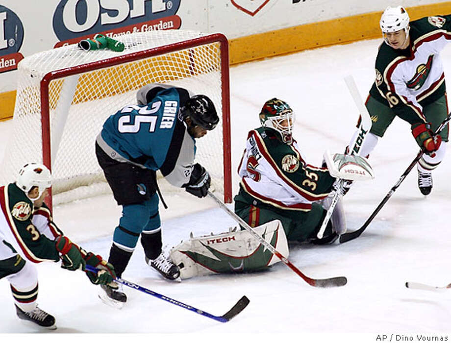San Jose Sharks' Mike Grier (35) flicks a shot under the pads of Minnesota Wild's goalie Manny Fernandez for the Sharks' first goal in the first period of an NHL hockey game, Tuesday, Nov. 7, 2006, in San Jose, Calif. (AP Photo/Dino Vournas) Photo: DINO VOURNAS