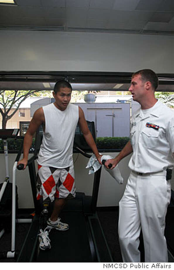 Paralympic athlete Casey Tibbs (right) speaks with Navy corpsman Nathaniel Leoncio (on treadmill) who lost his right leg after being injured in Iraq last year. Credit: NMCSD Public Affairs  Ran on: 11-08-2006  Paralympic athlete Casey Tibbs (right) chats with Petty Officer Third Class Nathaniel Leoncio. Photo: NMCSD Public Affairs